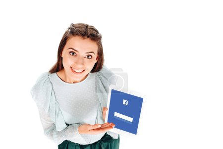 high angle view of cheerful woman with tablet with facebook logo on screen isolated on white