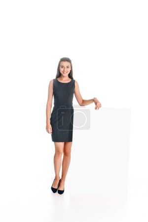 smiling woman in black dress with blank banner isolated on white