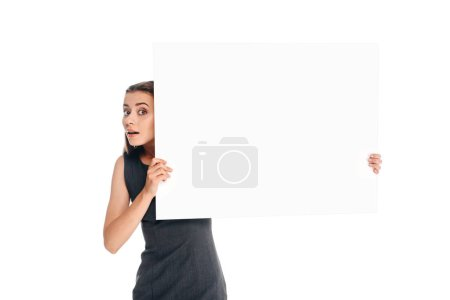 portrait of shocked young woman holding blank banner isolated on white
