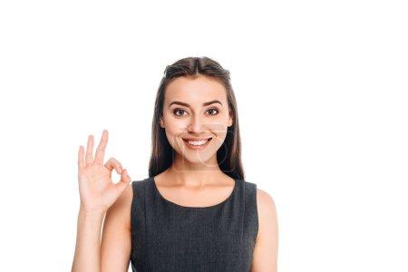 Porträt einer lächelnden Frau in einem eleganten schwarzen Kleid, das Ok-Zeichen isoliert auf Weiß zeigt
