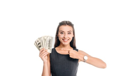 Photo for Smiling woman in black dress pointing at dollar banknotes isolated on white - Royalty Free Image