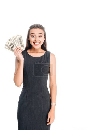 cheerful young woman in black dress holding dollar banknotes isolated on white