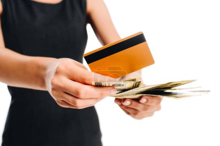 partial view of woman in black dress with credit card and cash isolated on white