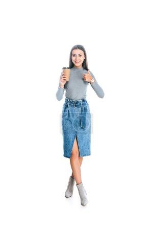 Photo pour Souriante jeune femme avec un café à aller montrer le pouce en haut isolé sur blanc - image libre de droit
