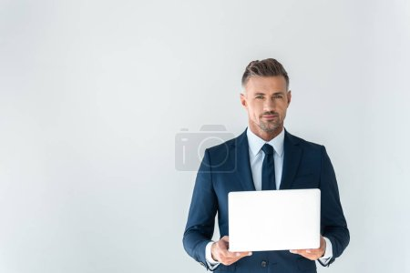 handsome businessman holding laptop and looking at camera isolated on white
