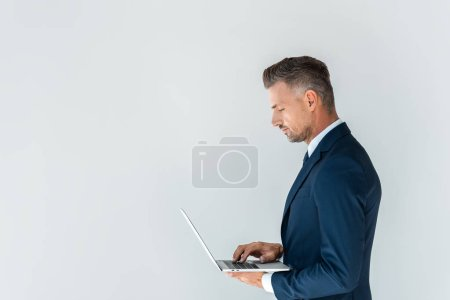 Photo for Side view of handsome businessman using laptop isolated on white - Royalty Free Image