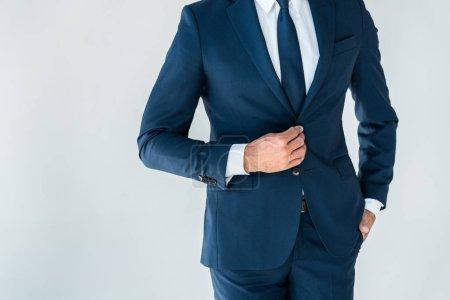 cropped image of businessman buttoning jacket isolated on white
