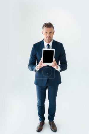 Photo for High angle view of handsome businessman showing tablet with blank screen isolated on white - Royalty Free Image