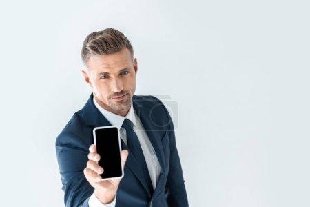 Photo pour Vue d'angle élevé de bel homme d'affaires montrant smartphone avec écran blanc et regardant la caméra isolé sur blanc - image libre de droit