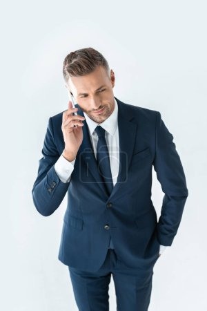 Photo for High angle view of handsome businessman in blue suit talking by smartphone isolated on white - Royalty Free Image