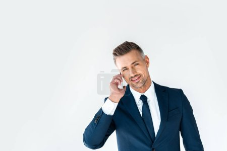 smiling handsome businessman talking by smartphone and looking at camera isolated on white