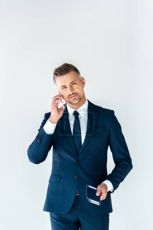 Photo for Cheerful handsome businessman talking by smartphone and looking at camera isolated on white - Royalty Free Image