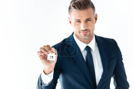 Photo for Selective focus of handsome businessman holding key from house and looking at camera isolated on white - Royalty Free Image