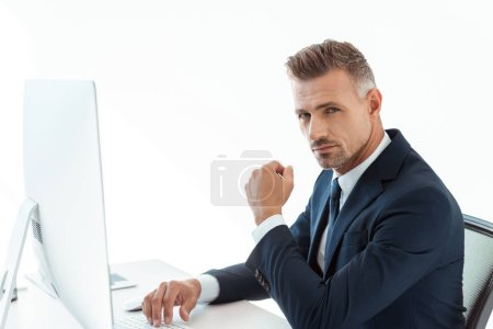handsome businessman sitting at table with computer and looking at camera isolated on white