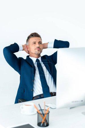 Photo pour Bel homme d'affaires en costume assis à table avec ordinateur et tenant les mains derrière la tête isolé sur blanc - image libre de droit