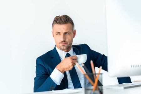 Photo for Handsome businessman holding cup of coffee and looking away isolated on white - Royalty Free Image