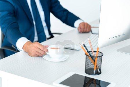 Photo pour Image recadrée d'un homme d'affaires prenant une tasse de café à table isolé sur blanc - image libre de droit