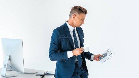 Photo pour Vue latérale d'un bel homme d'affaires tenant une tasse de café et lisant un journal isolé sur blanc - image libre de droit