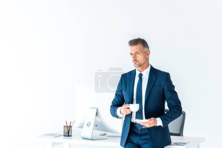 handsome businessman holding cup of coffee and looking at camera isolated on white