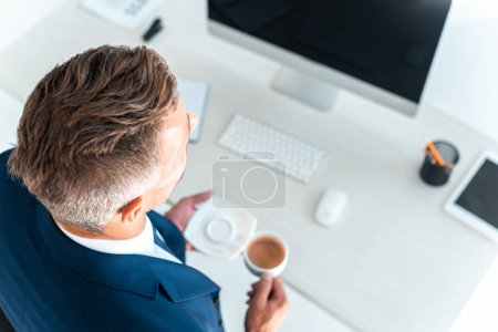 Photo for High angle view of businessman holding cup of coffee and plate near table in office - Royalty Free Image