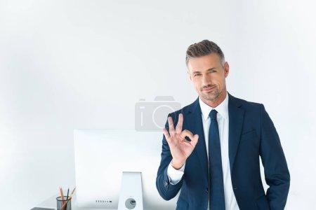 Foto de Hombre de negocios guapo mostrando bien gesto y mirando a cámara aislada en blanco - Imagen libre de derechos
