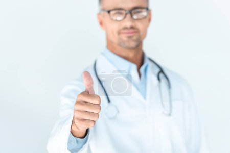 selective focus of handsome doctor in glasses with stethoscope on shoulders showing thumb up isolated on white
