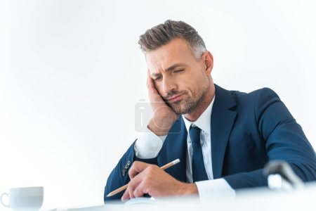 low angle view of tired businessman holding pencil and looking down at table isolated on white