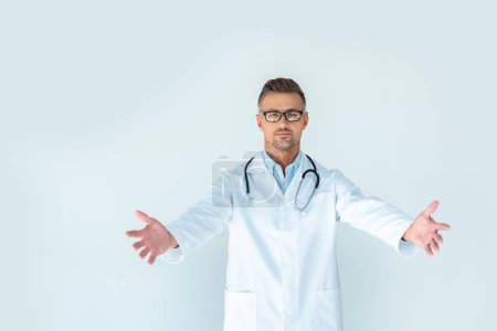 Photo pour Beau docteur dans des verres avec stéthoscope sur épaules debout avec les bras ouverts et en regardant la caméra isolé sur blanc - image libre de droit