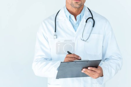 Photo for Cropped image of doctor with stethoscope on shoulders writing something in clipboard isolated on white - Royalty Free Image