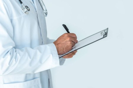 cropped image of doctor with stethoscope on shoulders writing something in clipboard isolated on white
