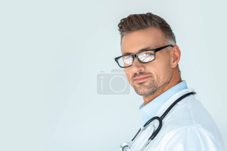 Photo for Portrait of handsome doctor in glasses with stethoscope on shoulders looking at camera isolated on white - Royalty Free Image