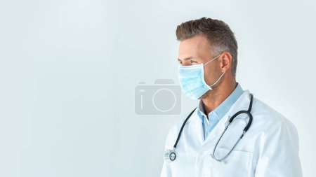 handsome doctor in medical mask looking away isolated on white