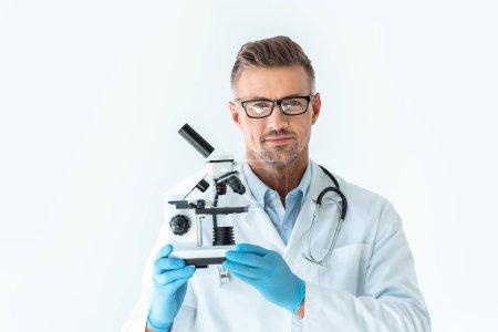 Foto de Científico guapo en los vidrios manteniendo microscopio y mirando a cámara aislada en blanco - Imagen libre de derechos