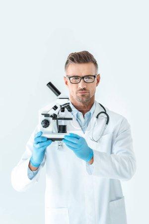 Foto de Científico serio guapo en vidrios manteniendo microscopio y mirando a cámara aislada en blanco - Imagen libre de derechos