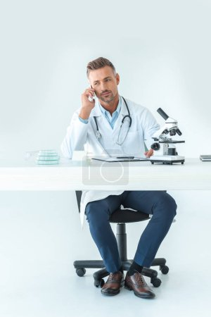 handsome scientist talking by smartphone at table with microscope isolated on white