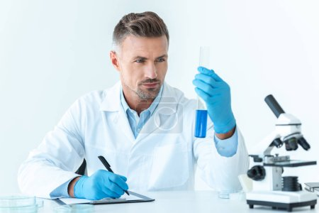 handsome scientist looking at test tube with blue reagent isolated on white