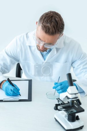 Photo for Handsome scientist in protective glasses writing about experiment isolated on white - Royalty Free Image