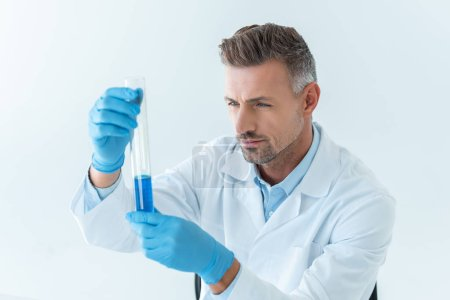 Photo for High angle view of handsome scientist looking at test tube with blue reagent isolated on white - Royalty Free Image