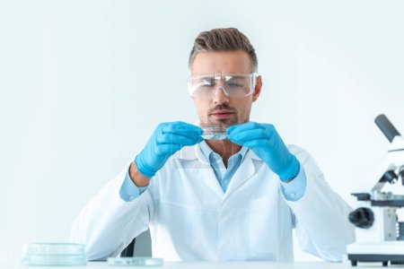 handsome scientist in protective glasses looking at reagent during experiment isolated on white