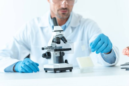 cropped image of scientist preparing for experiment with microscope isolated on white