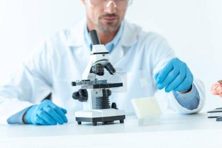 Foto de Imagen recortada de científico de la preparación para el experimento con microscopio aislado en blanco - Imagen libre de derechos