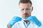 portrait of handsome scientist in protective glasses looking at reagent during experiment isolated on white