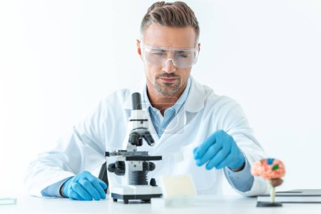 Photo for Selective focus of handsome scientist in protective glasses making experiment with microscope isolated on white - Royalty Free Image