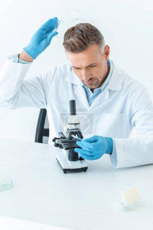 Foto de Apuesto científico usar gafas de protección y mirando al microscopio aislado en blanco - Imagen libre de derechos