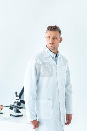 Foto de Apuesto científico permanente junto a la mesa con microscopio y mirando lejos, aislado en blanco - Imagen libre de derechos