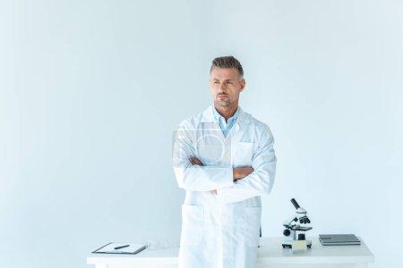 Foto de Científico apuesto de pie con los brazos cruzados cerca de mesa aislado en blanco - Imagen libre de derechos