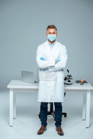 Photo for Handsome scientist in medical mask and medical gloves standing with crossed arms isolated on white - Royalty Free Image