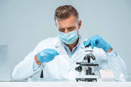 Photo for Handsome scientist in medical mask and medical gloves making test with microscope isolated on white - Royalty Free Image