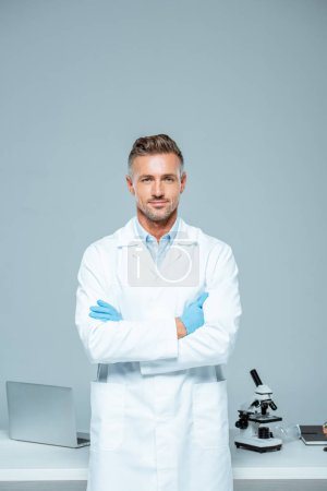 Photo for Handsome scientist in white coat and latex gloves standing with crossed arms and looking at camera isolated on white - Royalty Free Image