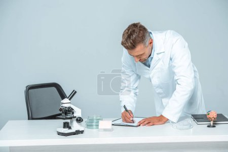Photo for Handsome scientist writing something to clipboard at table isolated on white - Royalty Free Image
